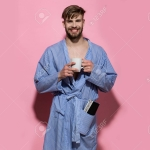 Happy bachelor in dressing gown smile with cup and magazine